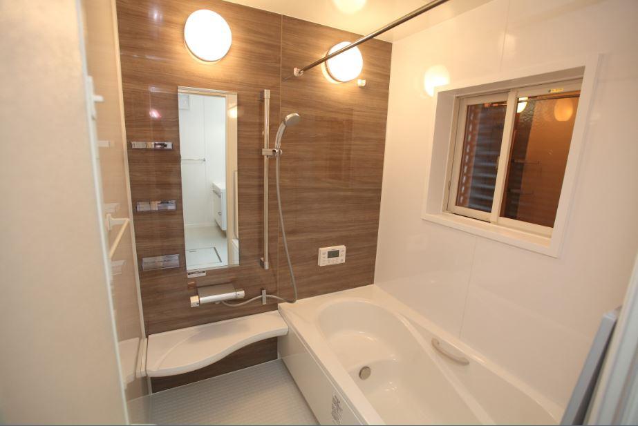 ウォールナットのアクセント壁で落ち着いた空間に。<br/> ベンチタイプの浴槽で半身浴をしながらくつろぎの時間を過ごせます。