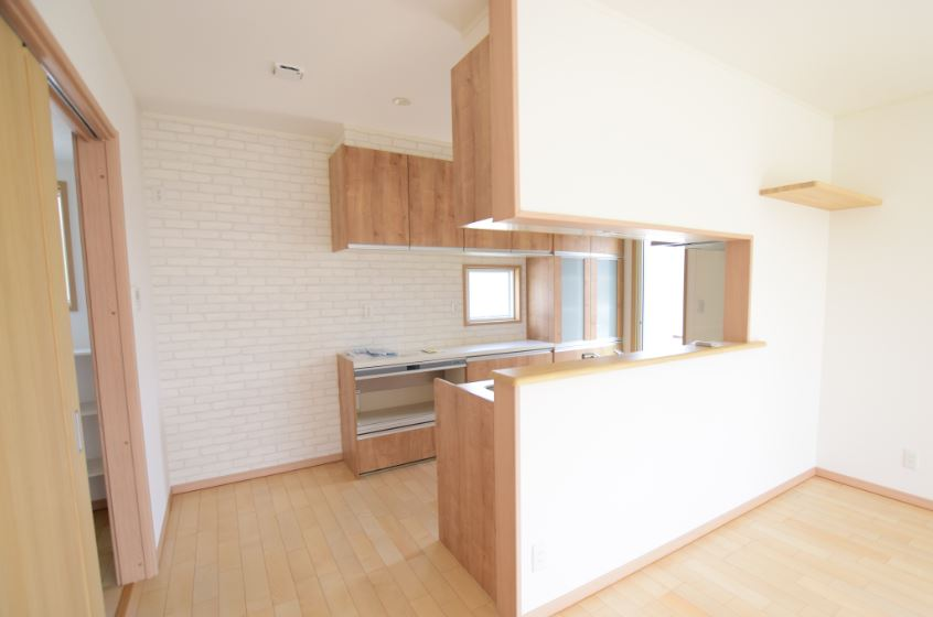 食器棚背面にはホワイトのタイル柄のアクセントクロスを使用<br/> 主張しすぎないシンプルなアクセントで、イマドキな空間となります