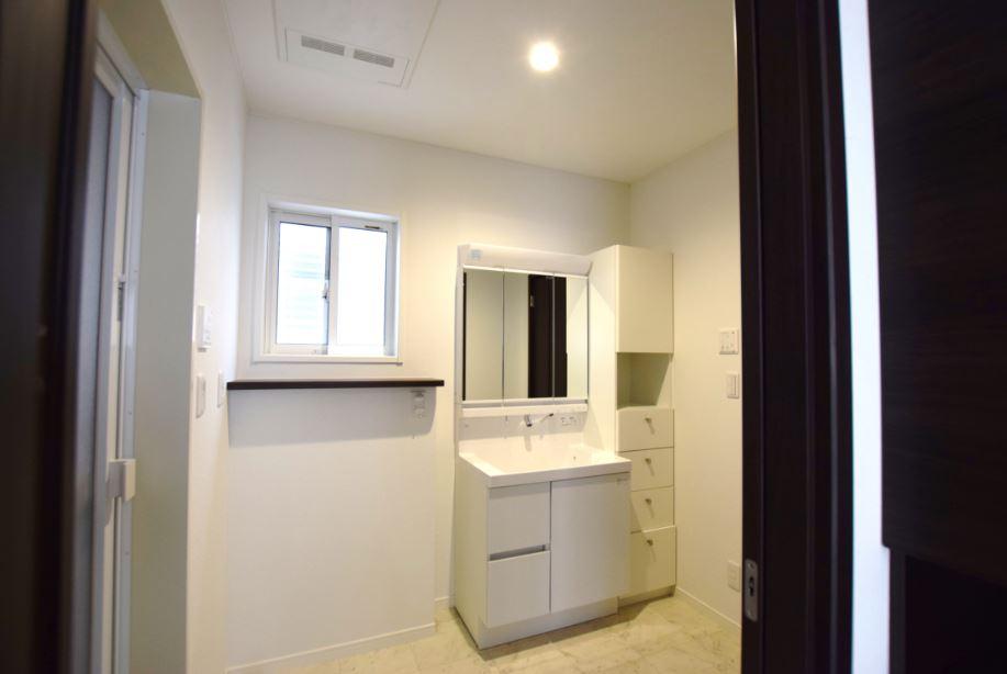 洗面脱衣室は広めにし、サニタリー収納を設置しました。<br/> 毎日使用するタオルや、浴室廻りで使用する物のストックを収納できます。<br/><br/> また、洗濯機の上には、毎日使う洗剤などを置くスペースを設けました。<br/> 各所に暮らしやすさの工夫が詰っています!