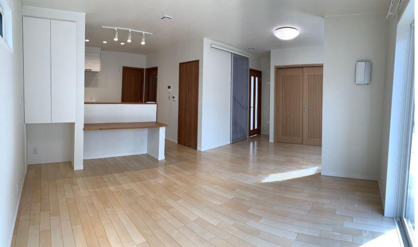 リビングからはホール(玄関)、洗面所・脱衣室、和室、二階に行くことができます。<br/> 動線の中心にリビングを配置することで、家事などのストレスを少なくすることができます。<br/><br/>   床 :プレシャスウッド / ハードメイプル<br/> 建 具: ウッディアート / ブラウングレイン<br/> 建 具:Jアート / ナチュラルグレイン<br/> 建 具:三協アルミ / アミス<br/><br/>  ※写真右側の壁にはシアスミンエアのイオンコントローラーを設置